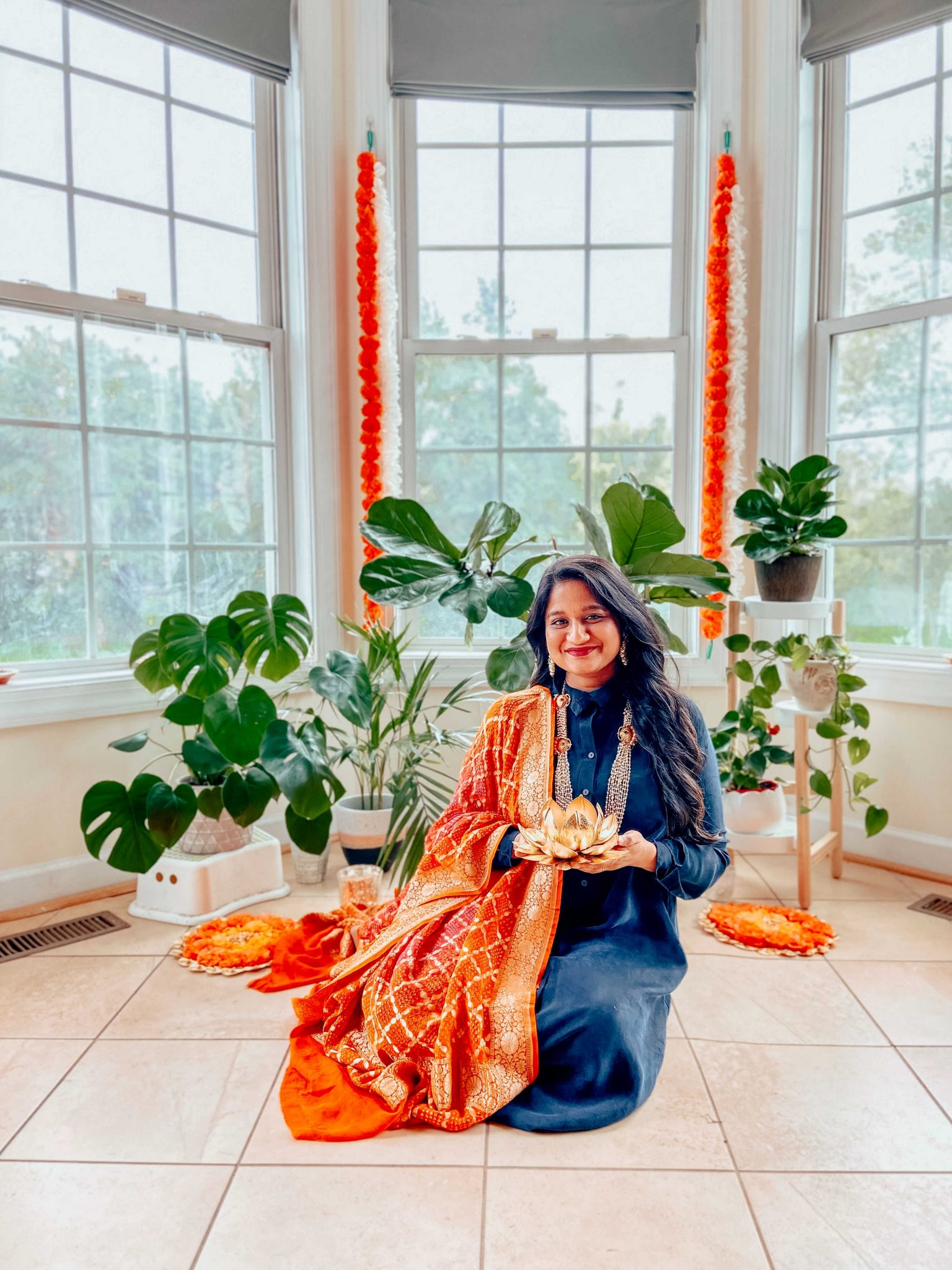 Simple Diwali Decoration ideas featured by top MD lifestyle blogger, Dreaming Loud |Diwali Decoration Ideas: image of a woman wearing Traditional Indian attire and sitting in a bay window area decorated with Wisteria garlands, Marigold Garlands, Curtain string lights, Silver Votives,Lotus diya,Colorful diya, Battery Tea lamps, and Plant stand.