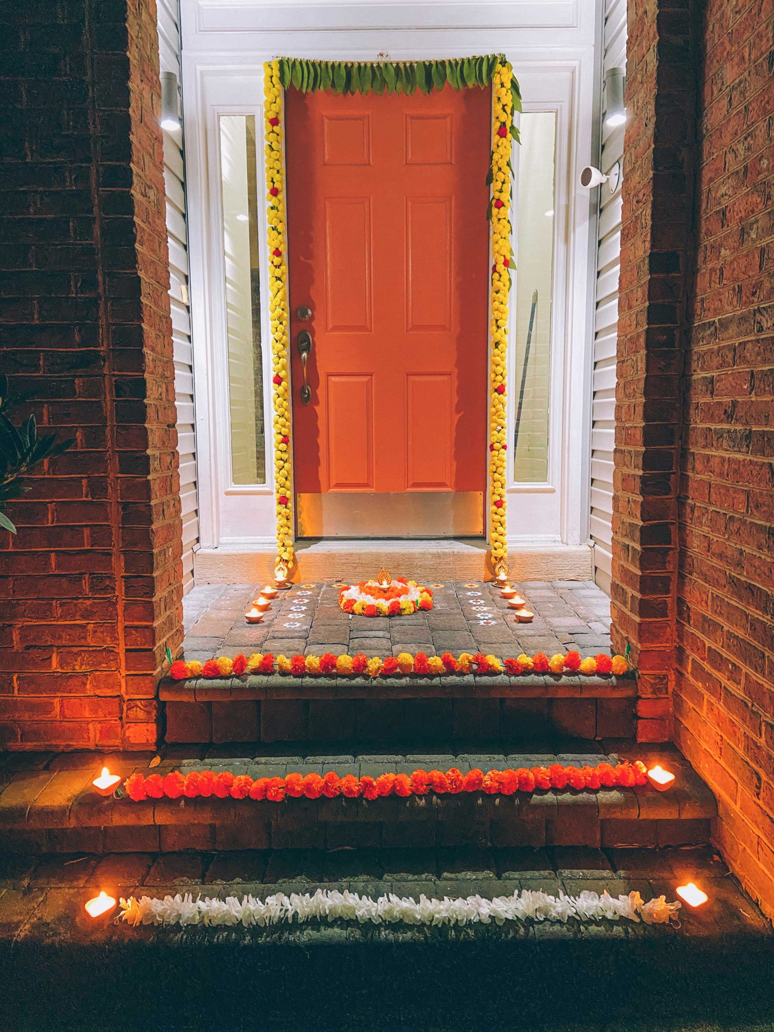Simple Diwali Decoration ideas featured by top MD lifestyle blogger, Dreaming Loud | Diwali Decoration Ideas: image of a front door and porch decorated with Mango Leaf Toran, Chrysanthemum garlands, Wisteria garlands,Marigold Garlands,Ganesh Diya, Rangoli Stencil, Rangoli Sand Colors, and Clay diyas.