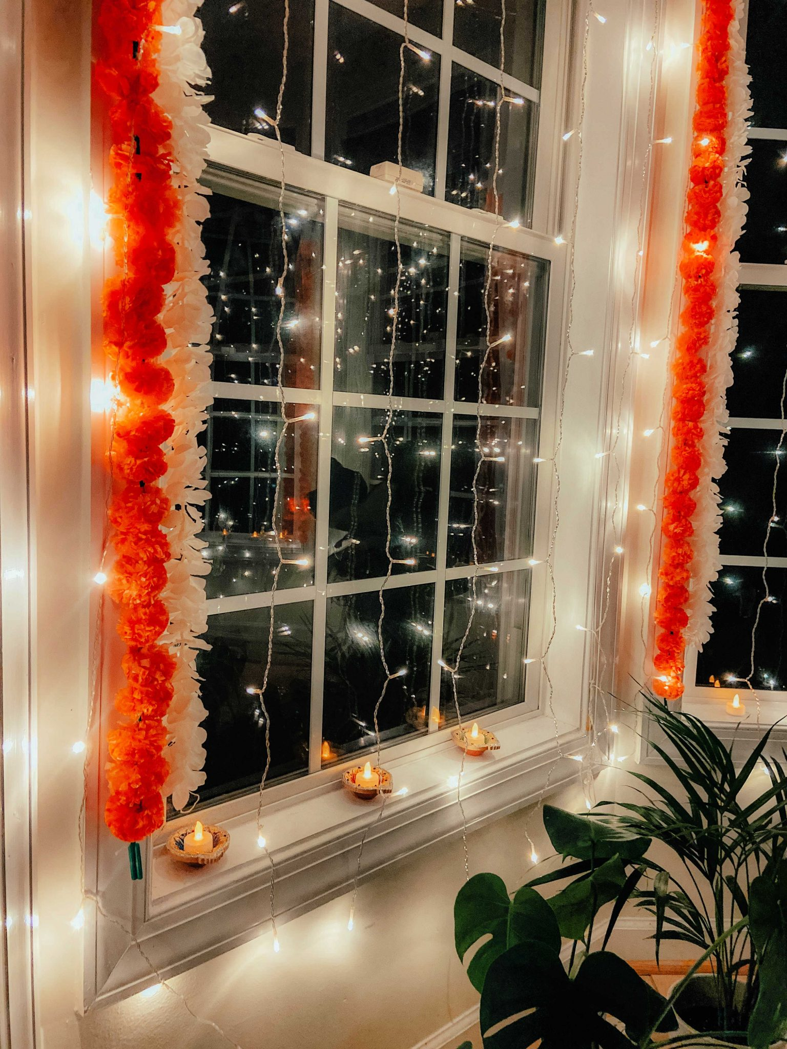 Simple Diwali Decoration ideas featured by top MD lifestyle blogger, Dreaming Loud |Diwali Decoration Ideas: image of a bay window area decorated with Wisteria garlands, Marigold Garlands, Curtain string lights, Silver Votives,Lotus diya,Colorful diya, Battery Tea lamps, and Plant stand.