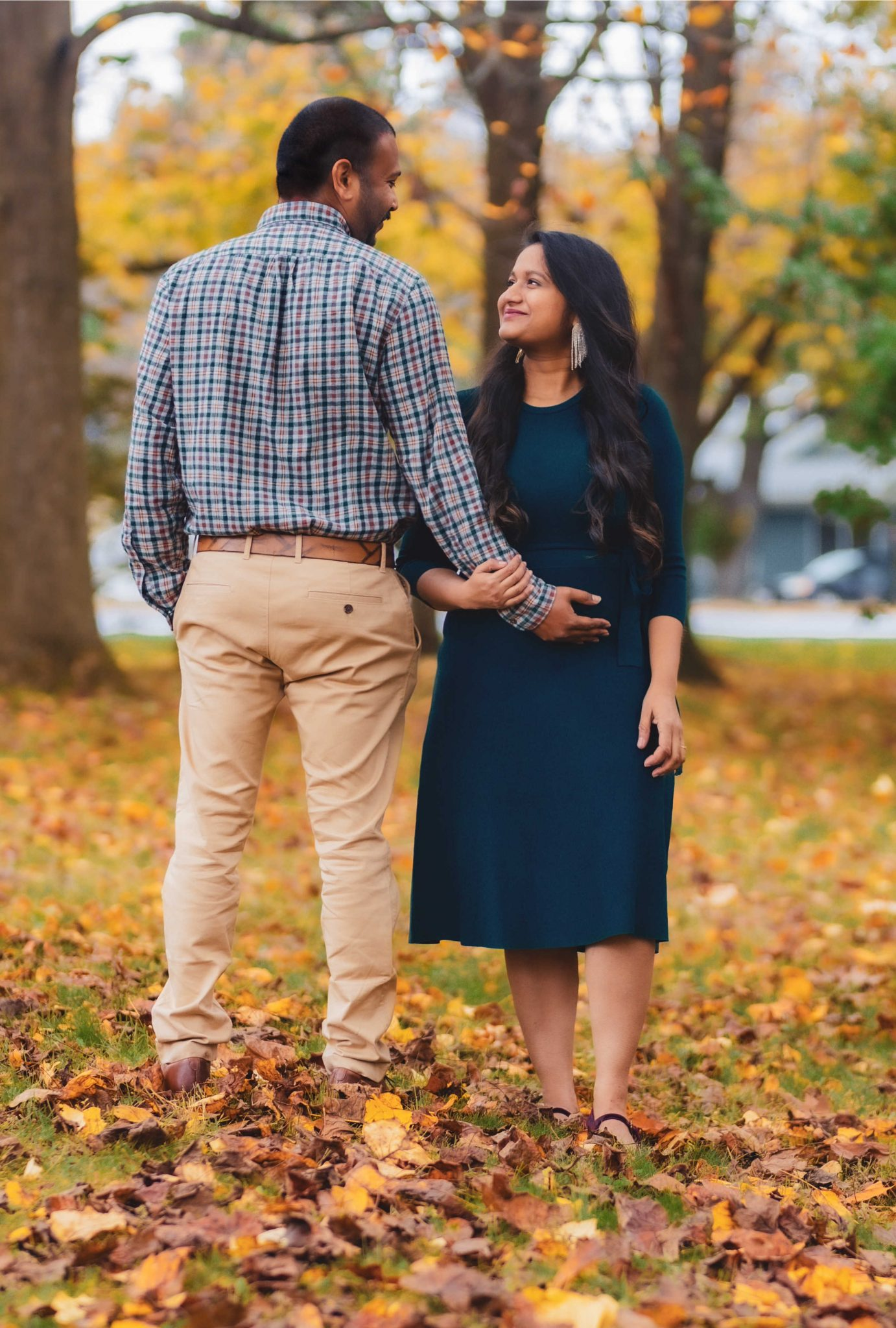 Fall Pregnancy Announcement by top Maryland life and style blogger, Dreaming Loud | Pregnancy Announcement by popular Maryland lifestyle blog, Dreaming Loud: image of a man wearing a blue and red plaid shirt and khaki pants and a pregnant woman wearing a blue maternity dress, statement earrings, and purple velvet shoes standing together outside under trees with yellow leaves.