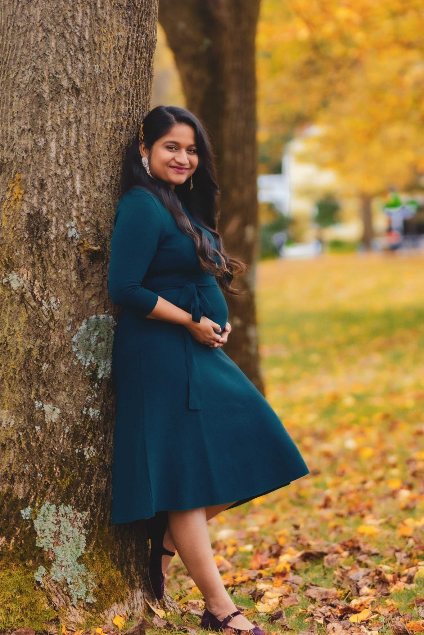Fall Pregnancy Announcement by top Maryland life and style blogger, Dreaming Loud   Pregnancy Announcement by popular Maryland lifestyle blog, Dreaming Loud: image of a pregnant woman leaning against a tree and wearing a blue maternity dress, statement earrings, and purple velvet shoes.
