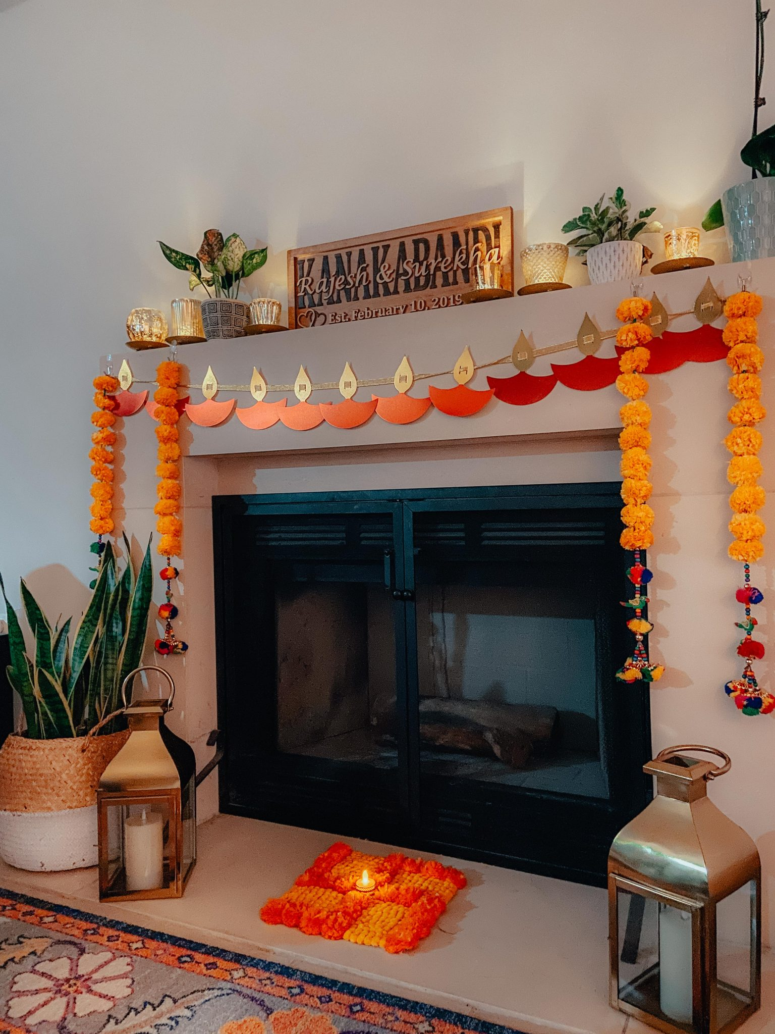Simple Diwali Decoration ideas featured by top MD lifestyle blogger, Dreaming Loud: Fire Place Diwali Decoration | Diwali Decoration Ideas: image of a fireplace decorated with a Diya Banner, Swastik mat, Marigold hangings c/o Kula Village, and Gold Votives.