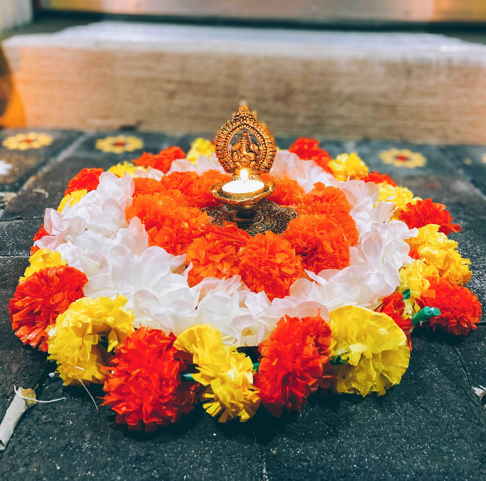Simple Diwali Decoration ideas featured by top MD lifestyle blogger, Dreaming Loud |Diwali Decoration Ideas: image of a front door and porch decorated with Chrysanthemum garlands, Wisteria garlands,Marigold Garlands,Ganesh Diya, Rangoli Stencil, Rangoli Sand Colors, and Clay diyas.