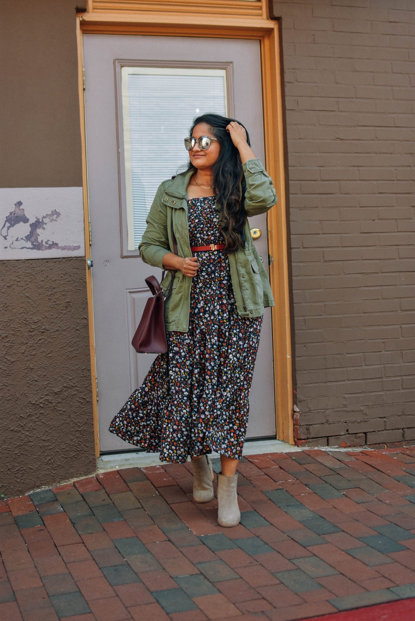 How to style utility jacket over dresses |Utility Jackets by popular Maryland modest fashion blog, Dreaming Loud: image of a woman wearing a Madewell Utility jacket with a floral print dress, brown leather belt, and brown suede ankle boots.