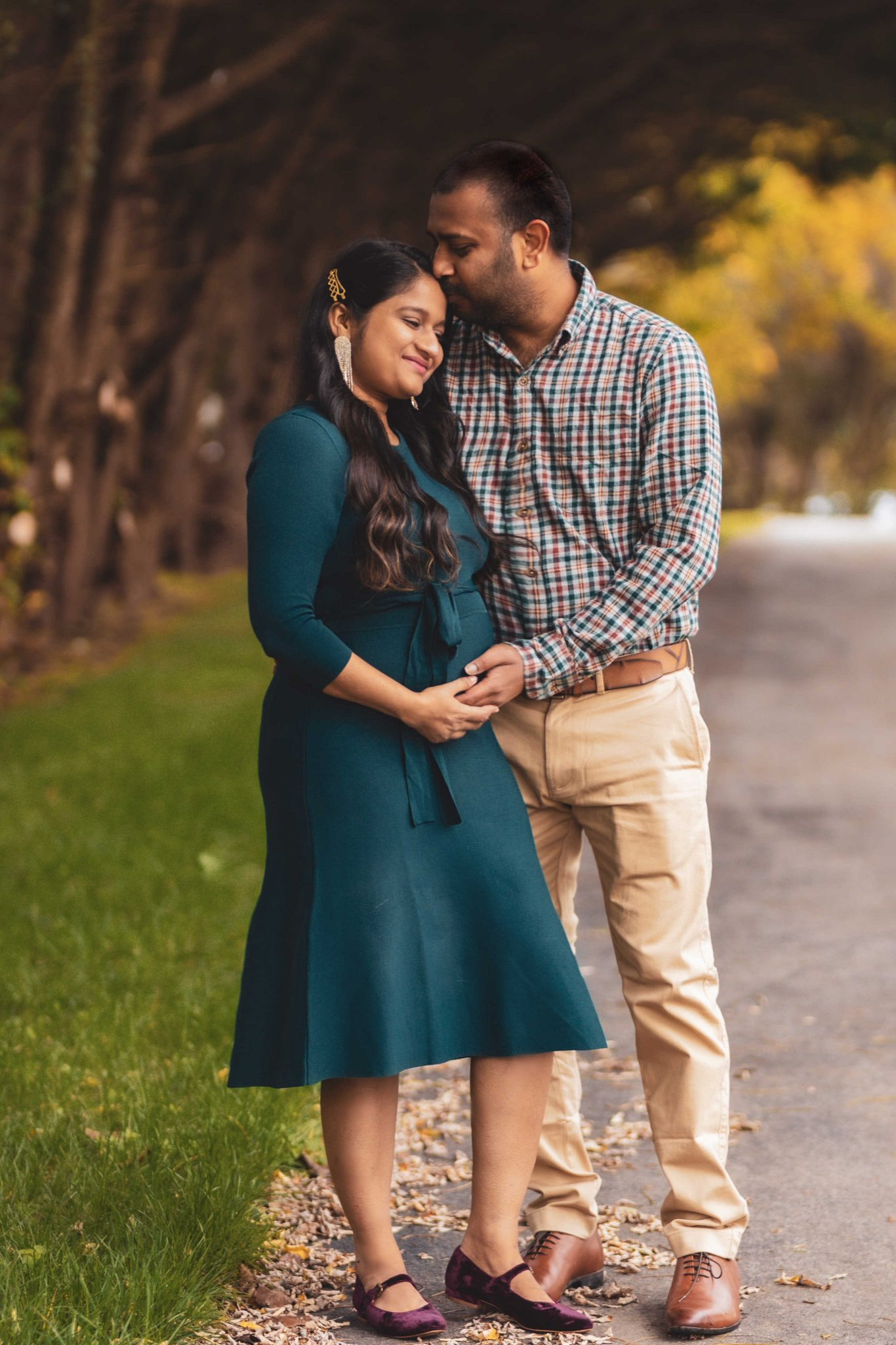 Fall Pregnancy Announcement by top Maryland life and style blogger, Dreaming Loud |Pregnancy Announcement by popular Maryland lifestyle blog, Dreaming Loud: image of a man wearing a blue and red plaid shirt and khaki pants and a pregnant woman wearing a blue maternity dress, statement earrings, and purple velvet shoes standing together outside under trees with yellow leaves.