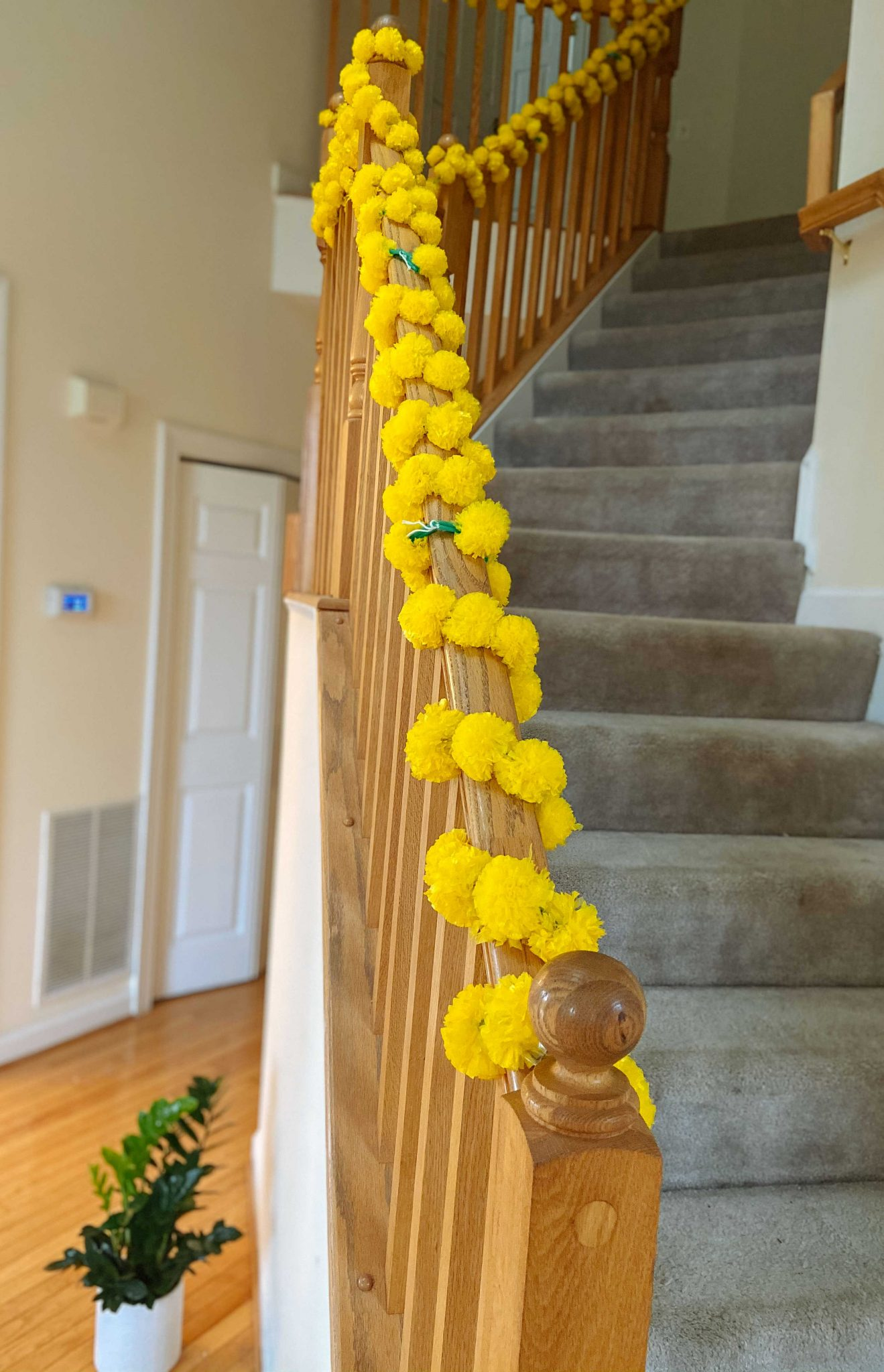 Simple Diwali Decoration ideas featured by top MD lifestyle blogger, Dreaming Loud: Staircase Diwali Decoration | Diwali Decoration Ideas: image of a fireplace decorated with a yellow marigold garland.