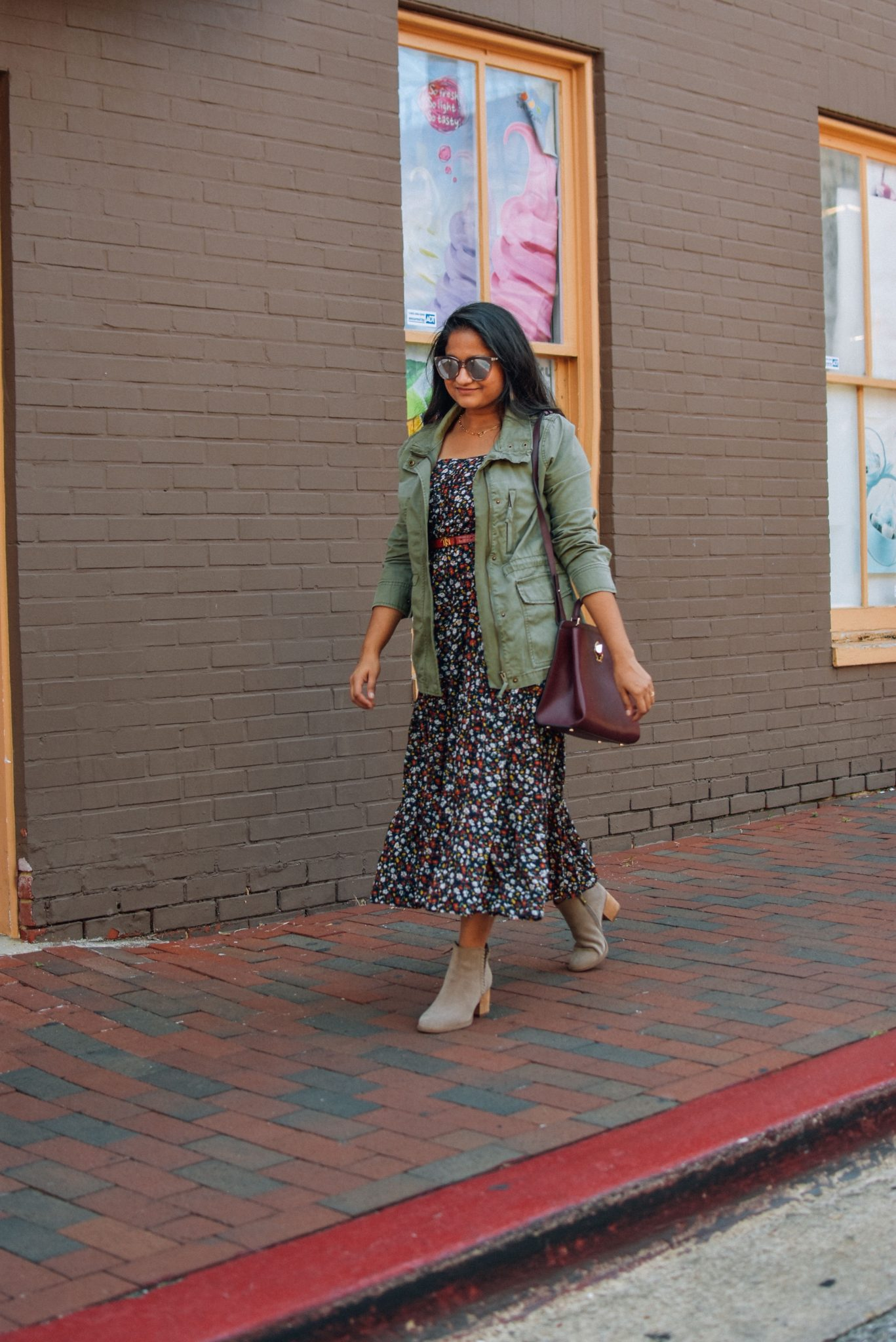 Utility Jackets by popular Maryland modest fashion blog, Dreaming Loud: image of a woman wearing a Madewell Utility jacket with a floral print dress, brown leather belt, and brown suede ankle boots.