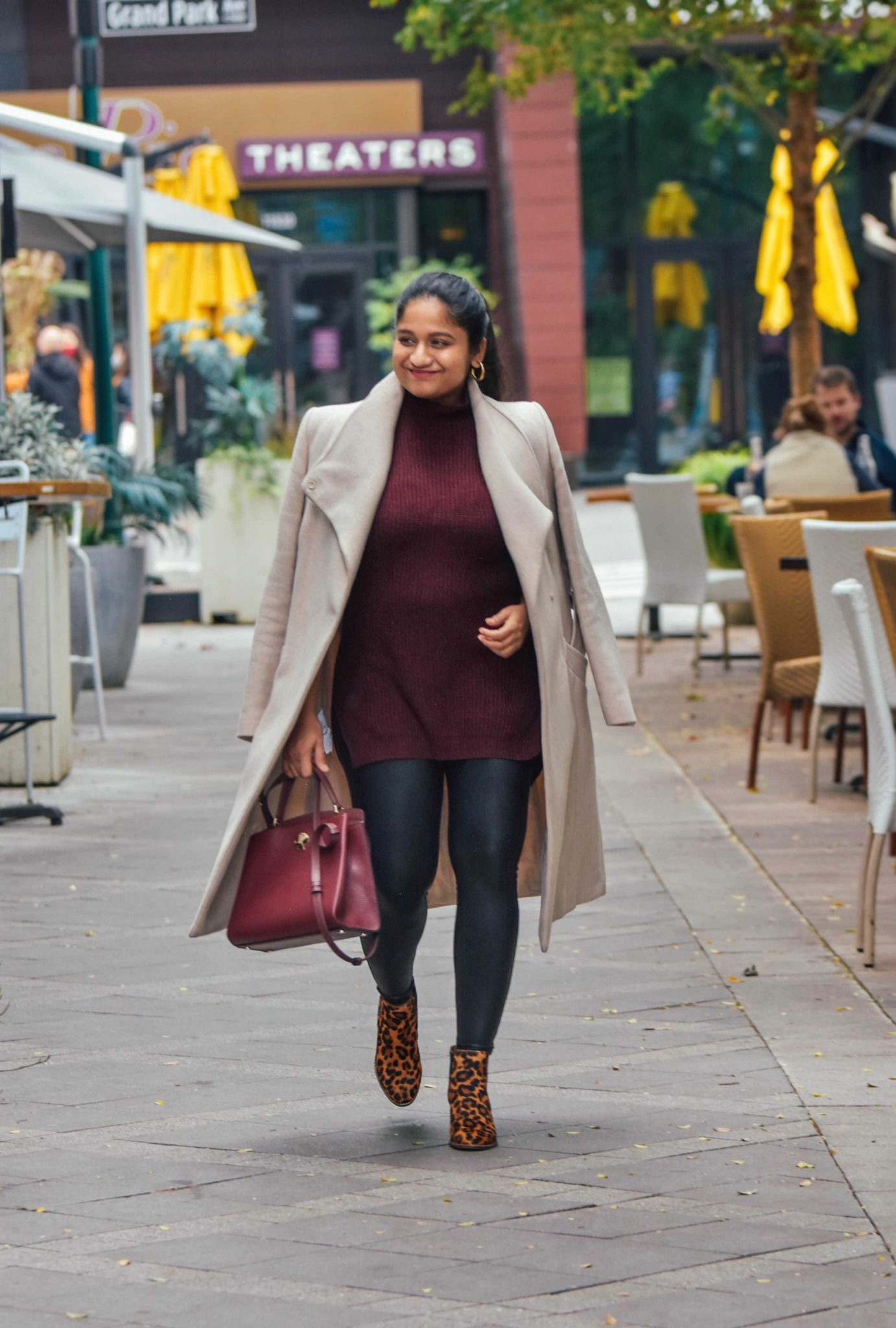 Style Spanx Faux leather legging, Mango belted Wrap coat in Ecru, Katespade Romy medium Satchel in Merlot-maternity style |Cute Thanksgiving Outfits by popular Maryland modest fashion blog, Dreaming Loud: image of a woman wearing Spanx Faux leather legging, wrap coat, leopard print boots and carrying a Kate spade Romy Satchel