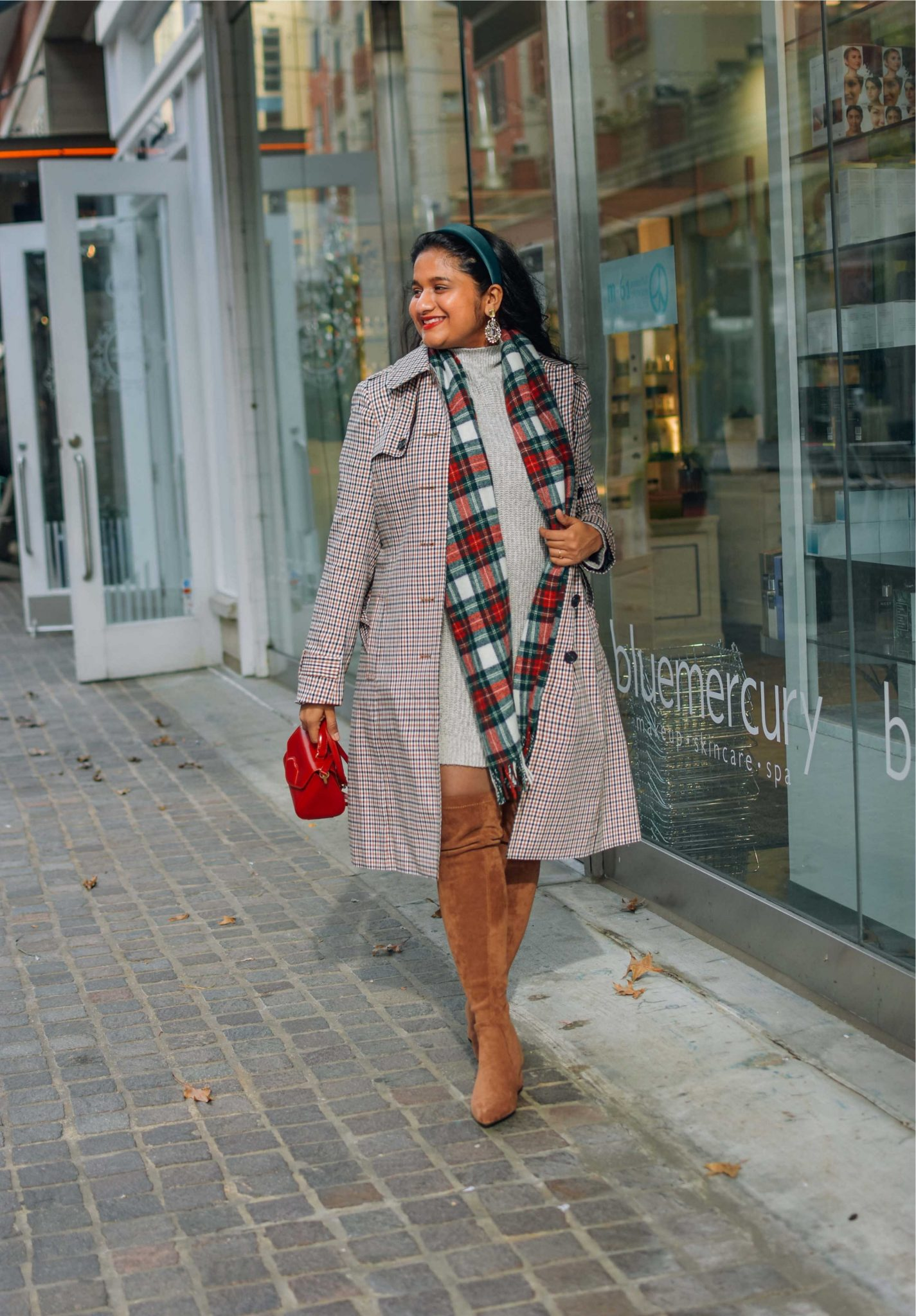 Wearing AE Sweater dress,Talbots polished plaid trench coat,Amazon OTK boots,J.crew Tartan scarf-Holiday Outfit ideas |Cute Holiday Outfit Ideas by popular Maryland modest fashion blog, Dreaming Loud: image of a woman wearing a AE Sweater dress, Amazon N.N.G OTK boots, J.crew Tartan scarf, and holding a lulu Guinness bag.