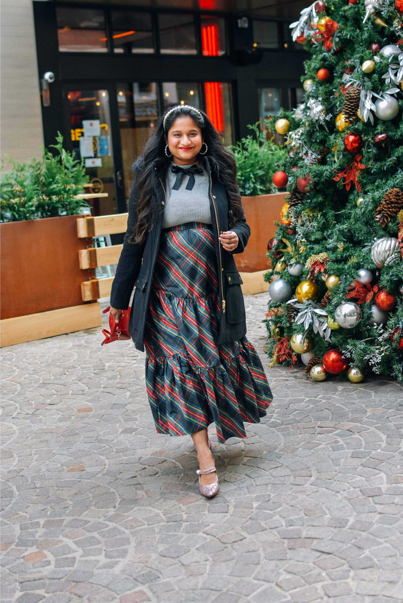 Wearing J.crew Chateau parka in Italian stadium-cloth wool in black, J.crew Tartan tiered sirt, bow sweater, Pink sequin pumps-Maternity Holiday Outfit ideas |Cute Holiday Outfit Ideas by popular Maryland modest fashion blog, Dreaming Loud: image of a woman wearing a J.crew Tartan Tartan skirt, grey sweater with black bow accent, pearl headband, J. Crew Chateau parka, and holding a Lulu Guinness bag.