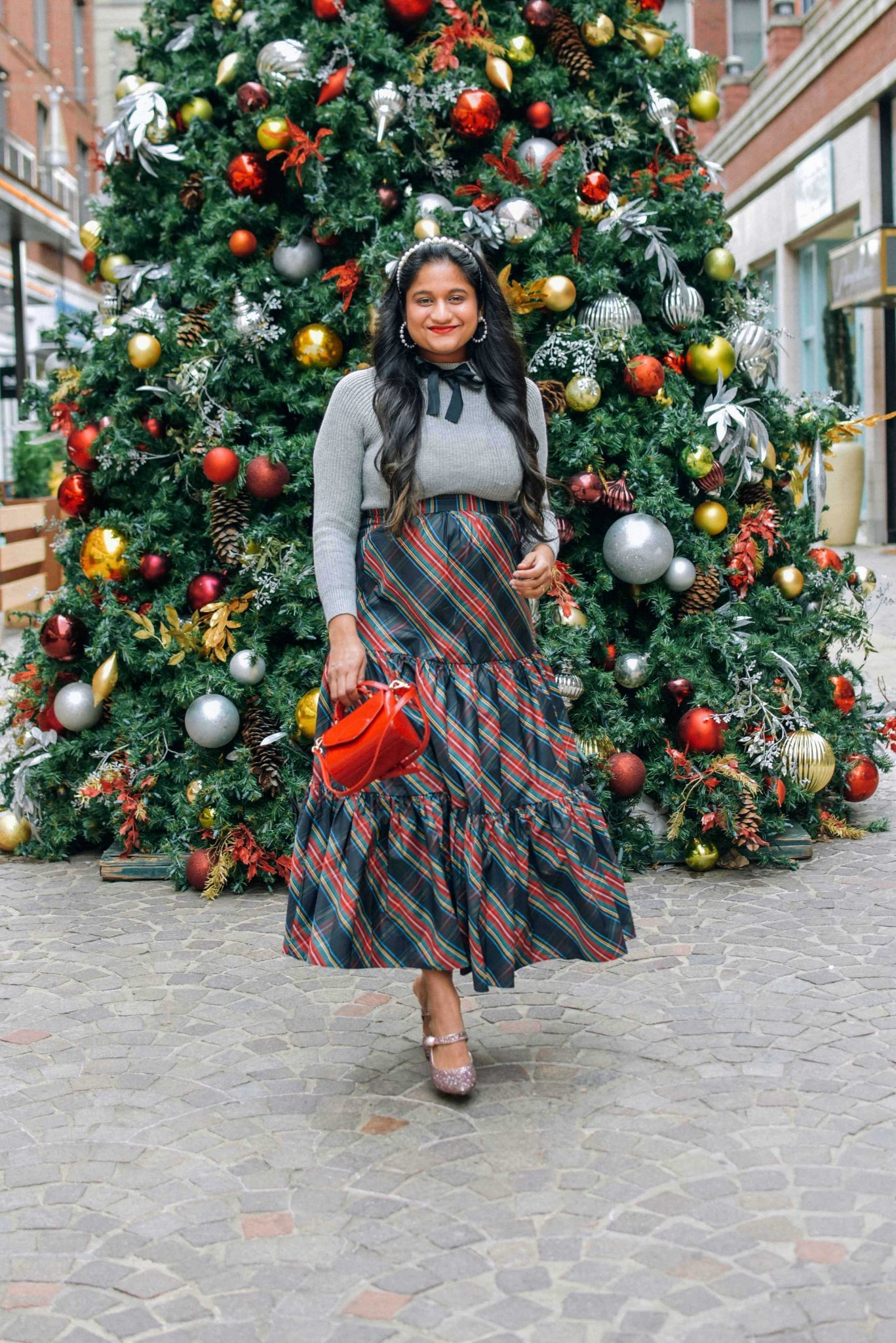 Wearing J.crew Tatran tiered sirt, bow sweater, Pink sequin pumps-Holiday Outfit ideas |Cute Holiday Outfit Ideas by popular Maryland modest fashion blog, Dreaming Loud: image of a woman wearing a J.crew Tartan Tartan skirt, grey sweater with black bow accent, pearl headband, and holding a Lulu Guinness bag.