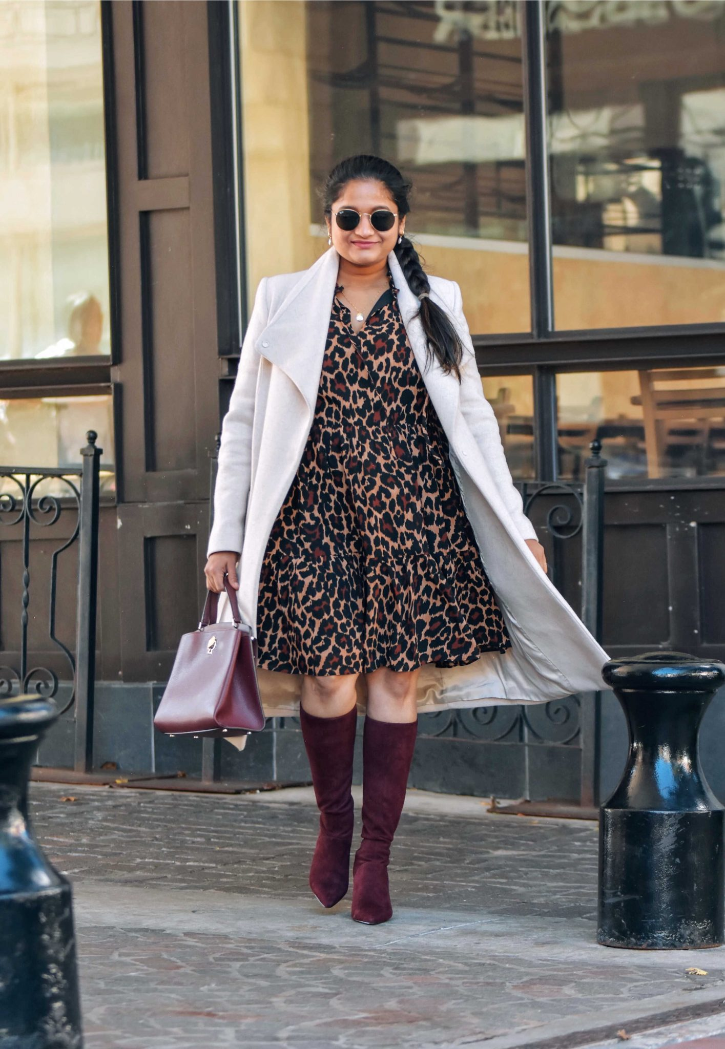 Wearing J.crew Tie-neck tiered dress in leopard crinkle chiffon, mango Belted wool coat, Boden Round Toe Stretch Burgundy boots-Holiday Outfit Ideas |Cute Holiday Outfit Ideas by popular Maryland modest fashion blog, Dreaming Loud: image of a woman wearing a J.crew Tie-neck tiered dress in leopard crinkle chiffon, mango Belted wool coat, and Boden Round Toe Stretch Burgundy boots.