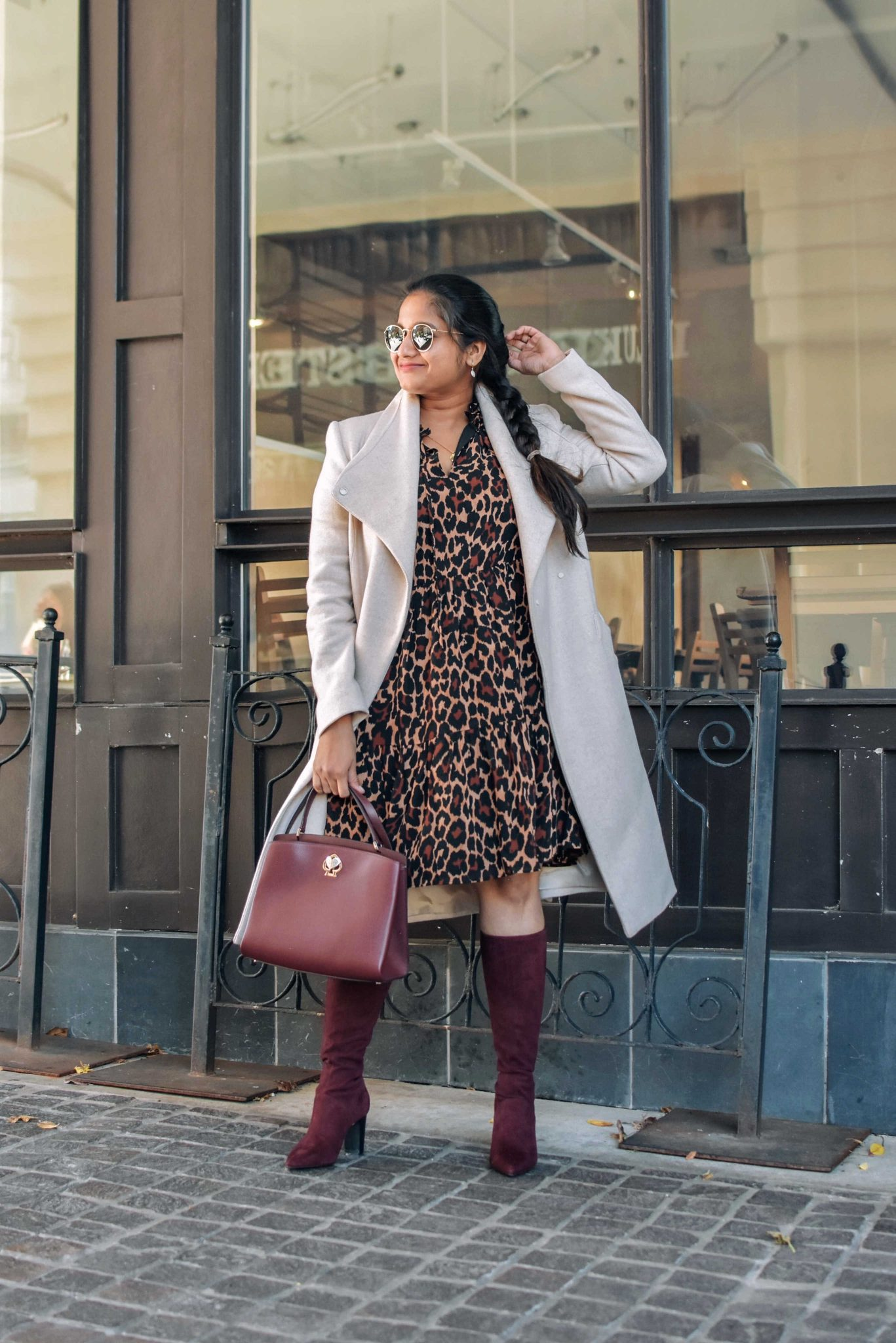 Wearing J.crew Tie-neck tiered dress in leopard crinkle chiffon, mango Belted wool coat, Boden Round Toe Stretch Burgundy boots | Cute Holiday Outfit Ideas by popular Maryland modest fashion blog, Dreaming Loud: image of a woman wearing a J.crew Tie-neck tiered dress in leopard crinkle chiffon, mango Belted wool coat, and Boden Round Toe Stretch Burgundy boots.