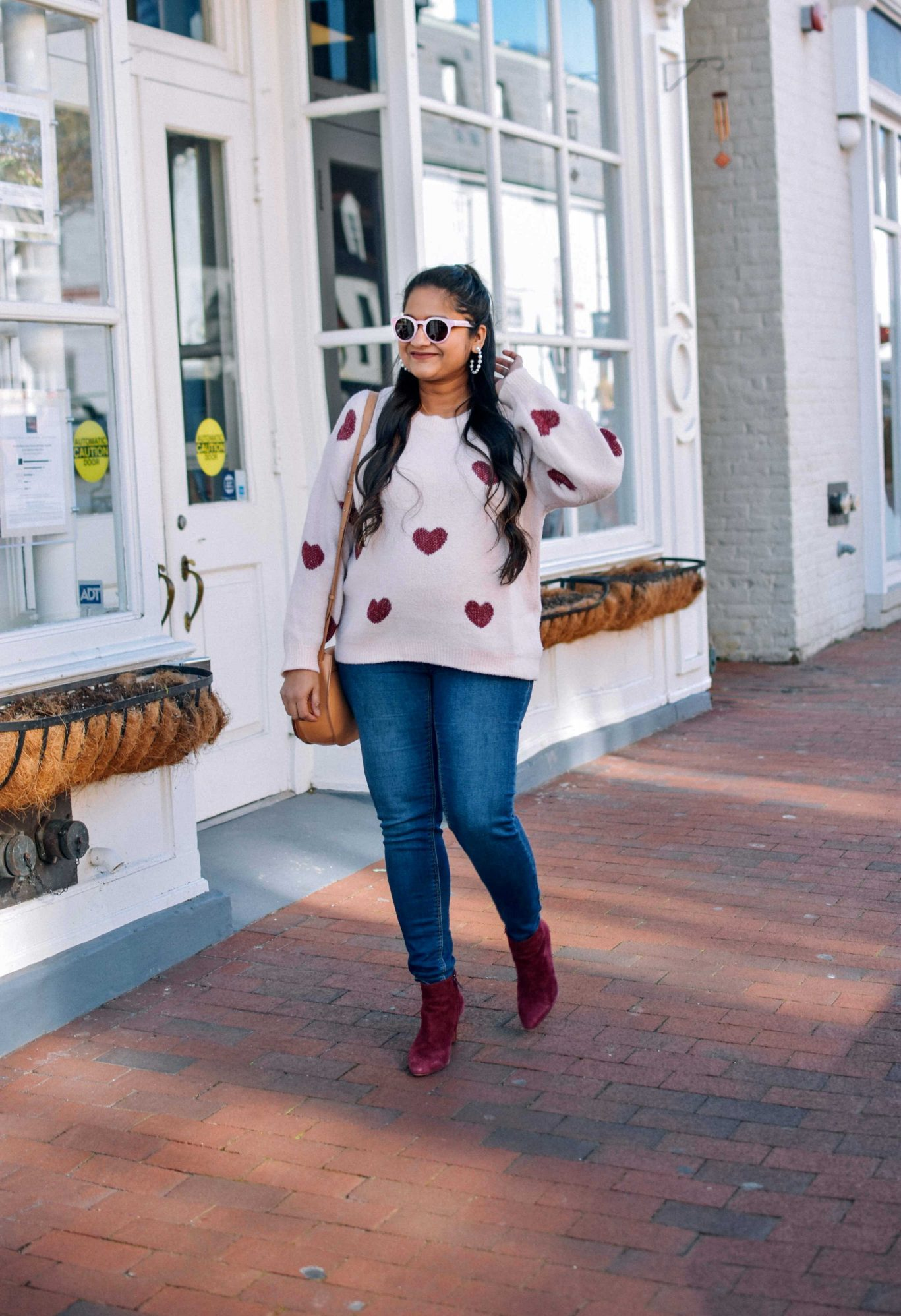 pregnancy Valentines day outfit-wearing pinklilly fuzzy Heart Pink Sweater, mango maternity jeans, Cuyana saddle bag, Illesteva pink sunglasses, Burgundy booties |Valentine's Day Outfit idea by popular Maryland modest fashion blog, Dreaming Loud: image of a woman wearing a heart print sweater, maternity skinny jeans, red suede ankle boots, and a Cuyana bag.