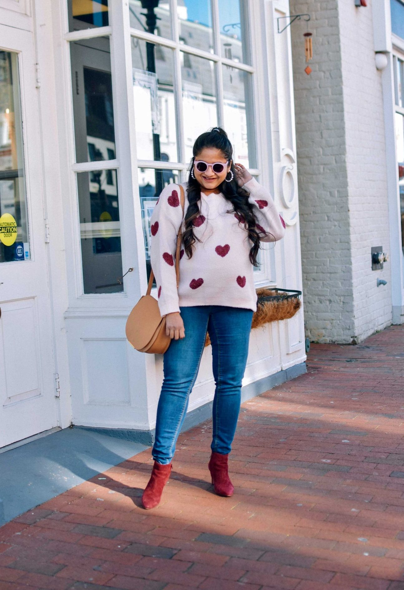 pregnancy Valentines day outfit-wearing pinklilly fuzzy Heart Pink Sweater, mango maternity jeans, Cuyana saddle bag, Illesteva pink sunglasses, Burgundy booties |Valentine's Day Maternity Outfit by popular Maryland modest fashion blog, Dreaming Loud: image of a pregnant woman wearing a heart print sweater, maternity skinny jeans, and red suede ankle boots.