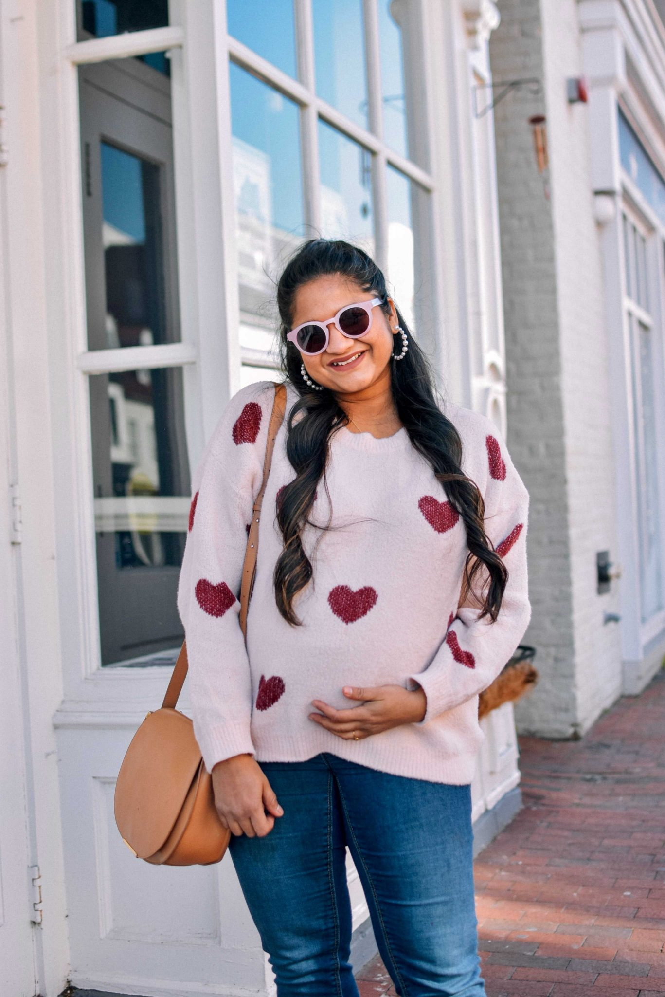 pregnancy Valentines day outfit-wearing pinklilly fuzzy Heart Pink Sweater, mango maternity jeans, Cuyana saddle bag, Illesteva pink sunglasses |Valentine's Day Outfit idea by popular Maryland modest fashion blog, Dreaming Loud: image of a woman wearing a heart print sweater, maternity skinny jeans, red suede ankle boots, and a Cuyana bag.