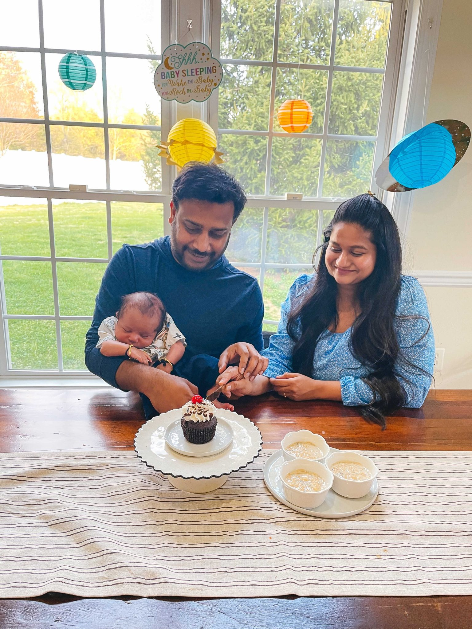 1 month with our baby boy Vihaan1 |1 Month Baby by popular Maryland motherhood blog, Dreaming Loud: image of a husband and wife sitting together at a table while holding their one month old baby and cutting into a cupcake.