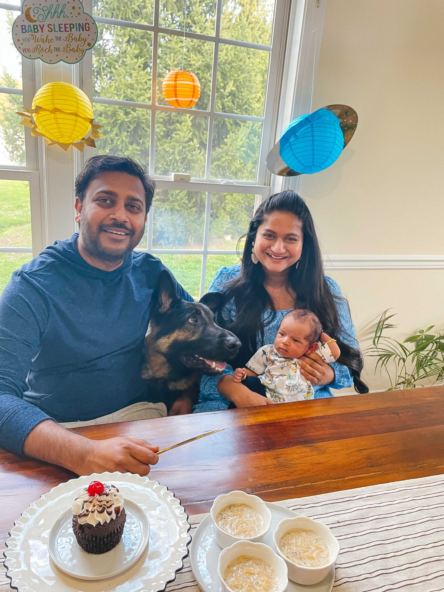1 month with our baby boy Vihaan4 |1 Month Baby by popular Maryland motherhood blog, Dreaming Loud: image of a husband and wife sitting together and holding their 1 month old baby boy.