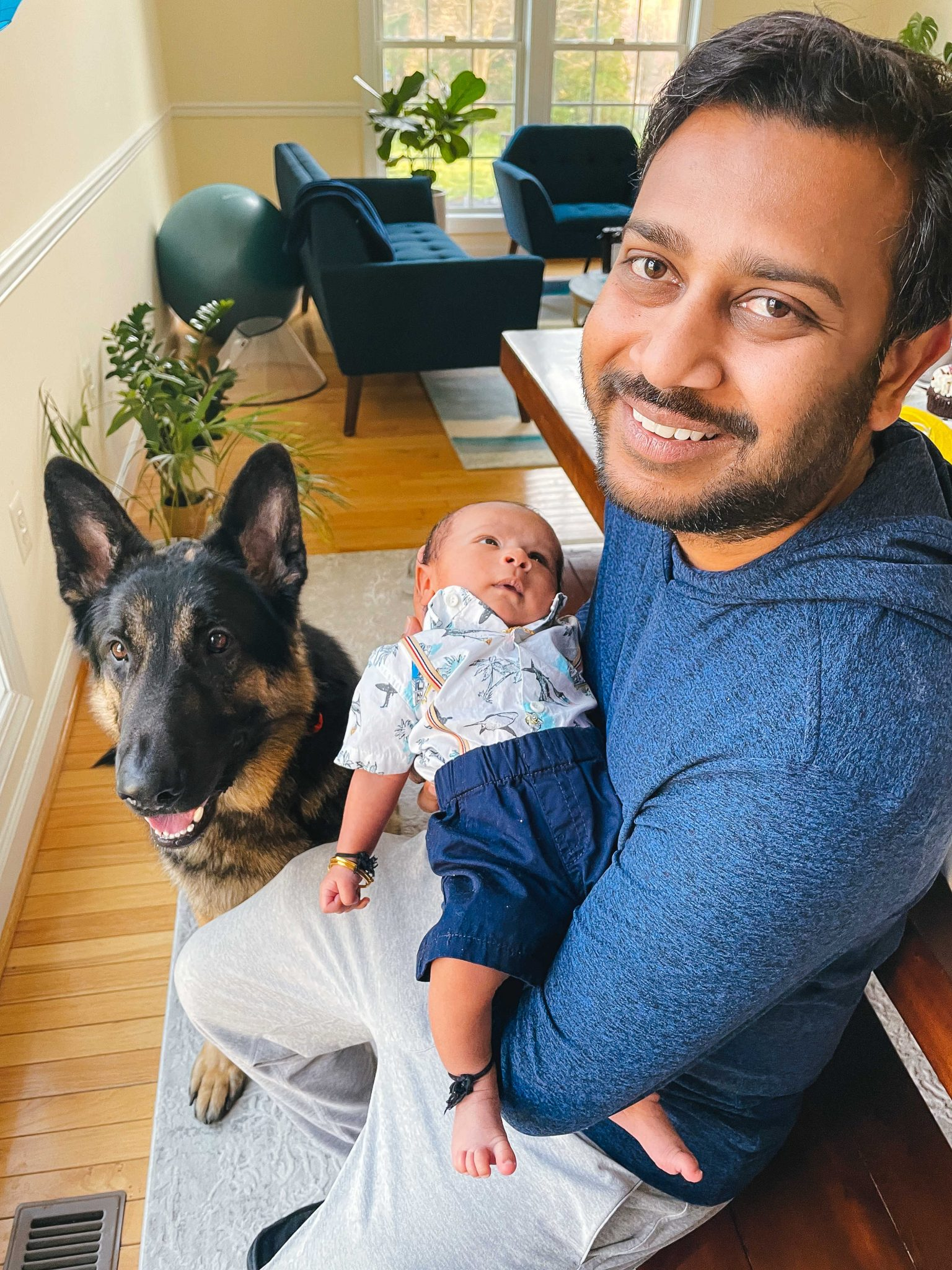 1 month with our baby boy Vihaan5 |1 Month Baby by popular Maryland motherhood blog, Dreaming Loud: image of a man sitting next to a German Shepard and holding a 1 month old baby boy.