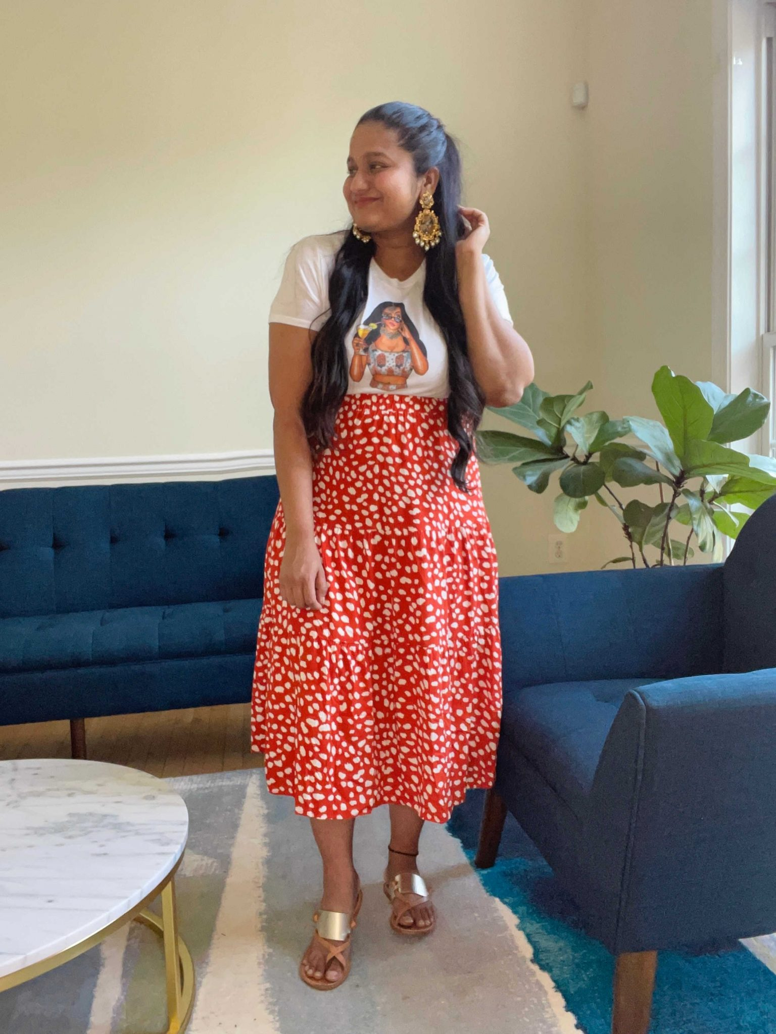 Wearing Amazon red printed midi skirt, Holi chic by Megha Margarita - cropped tee, Soludos Slotted Thong Sandals, Radha Krishna statement earrings. | Amazon Printed Midi Skirt by popular Maryland modest fashion blog, Dreaming Loud: image of a woman wearing a Amazon red and white floral print midi skirt, gold strap sandals, graphic t-shirt, and gold statement earrings.