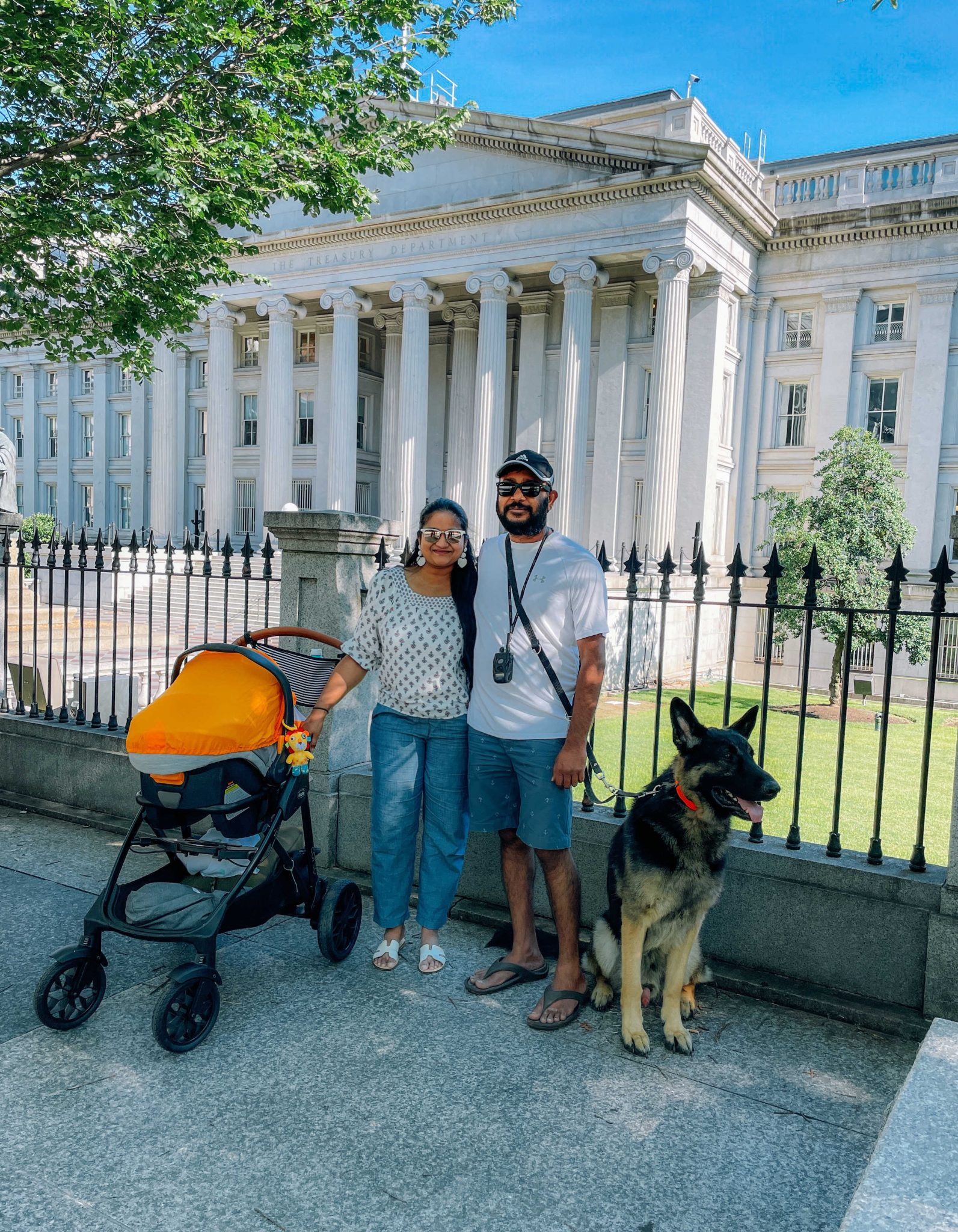 Summer Men Fashion Finds | Summer Fashion Trends by popular Maryland modest fashion blog, Dreaming Loud: image of a husband and wife sanding in front of a historic government building with their German Shepard dog and baby that's in a stroller and wearing  black and white 3/4 length sleeve blouse, chambray jogger pants, white t-shirt, baseball hat, chambray shorts, brown flip flops, and white t-strap sandals.