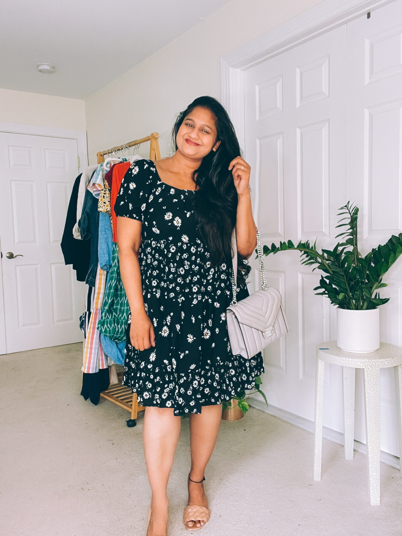 Wearing Maurices BLACK DAISY OFF THE SHOULDER BABYDOLL DRESS, Michael Kors hitney Quilted Leather Shoulder Bag by top US modest fashion blogger dreaming loud | Babydoll Dress by popular Maryland fashion blog, Dreaming Loud: image of a woman wearing a black and white daisy print Maurice's babydoll dress, tan braided strap sandals, and holding a grey handbag.