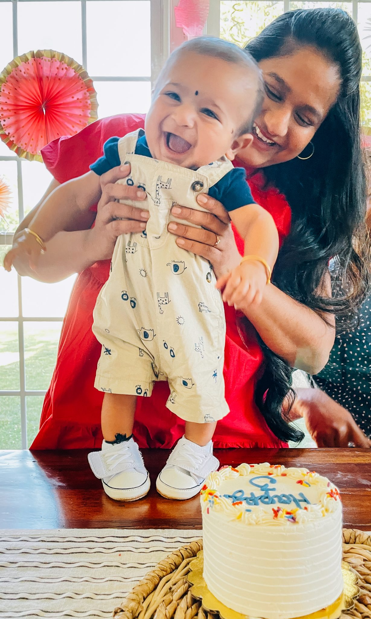 Sadu Bottu Recipe (DIY Black Bindhi for Babies) by top maryland mom blog dreaming loud | Sadu Bottu by popular Maryland motherhood blog, Dreaming Loud: image of a mom holding her young baby in front of a white layer cake.